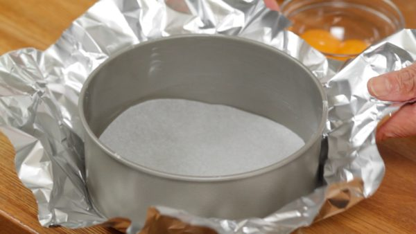 Place a piece of parchment paper cut to fit into the bottom of the pan. Then, cover the outside of the pan with a large piece of aluminum foil.