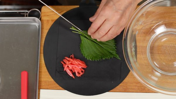 Next, cut the shiso leaves in half lengthwise and remove the stalks. Stack the leaves and cut them into thin strips. Cut the beni shoga, thin strips of pickled ginger into fine pieces.