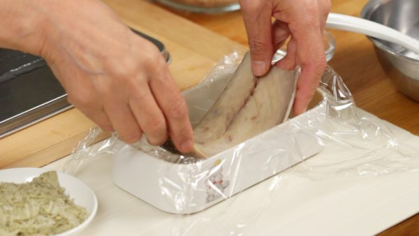Cover a bento box with a plastic wrap and place in the shime saba with the skin side facing down.