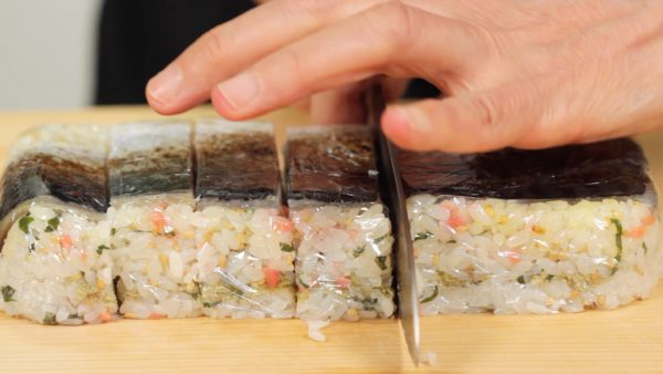 Flip the bento box and remove the pressed sushi. Wet the blade of a knife thoroughly. Make a cut in the plastic wrap and then slice off the oshizushi. You should clean the blade each time you cut off a slice. If the blade is coated with rice, it will be difficult to make clean cuts.