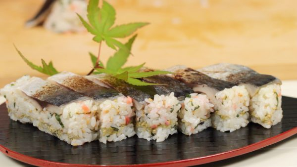 Now, remove the plastic wrap. Arrange the oshizushi onto a plate. Finally, garnish with the autumn colored leaves.