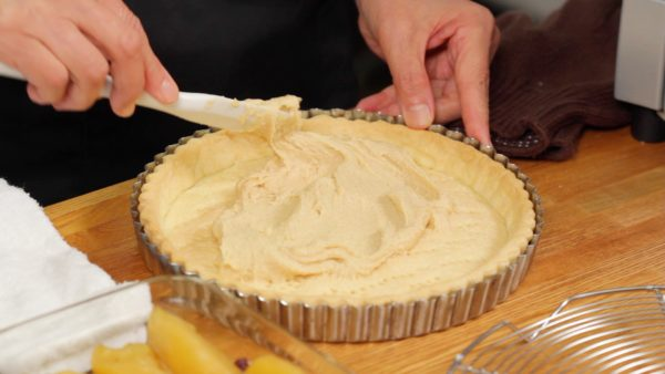 Let's fill the tart crust. Place the almond cream onto the bottom of the crust. Spread it with a spatula evenly.