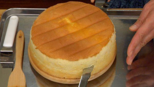 Nun lasst uns die Torte machen. Zieht das restliche Backpapier vom Kuchen ab und setzt diesen auf ein Drehteller. Bevor ihr den Kuchen in zwei Scheiben schneidet, zeichnet mit dem Messer eine Linie, während ihr den Kuchen mit dem Teller dreht. Schneidet den Kuchen horizontal entlang der Linie, sodass ihr einen geraden Schnitt bekommt. Setzt den oberen Teil des Kuchen auf ein Blech mit der geschnittenen Seite nach oben.