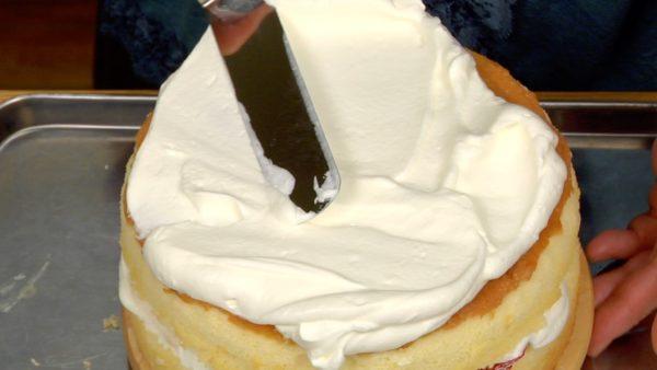 Zum Bedecken der Torte verwendet großzügig Sahne und streicht diese gleichmäßig auf der Oberfläche aus, indem ihr den Tortenteller dreht.
