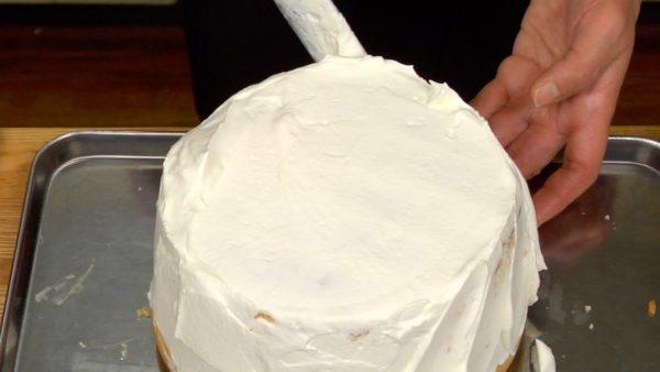 Sobald die Sahne an den Tortenrändern überläuft nehmt den Tortenspachtel vertikal zur Torte in die Hand und verteilt die Sahne entlang des Tortenrandes. Zieht die Tortenspachtel am Tortenrand schräg nach oben um ein dekoratives Muster entstehen zu lassen. Zieht dann die Tortenspachtel an der Oberfläche von außen nach innen, um die runde Form des Kuchens hervorzubringen.