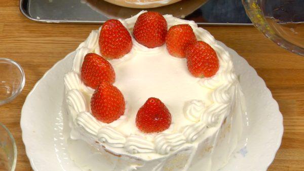 Hebt dann die Torte mit der Tortenspachtel auf ein Servierteller und platziert die Erdbeeren auf der Torte.