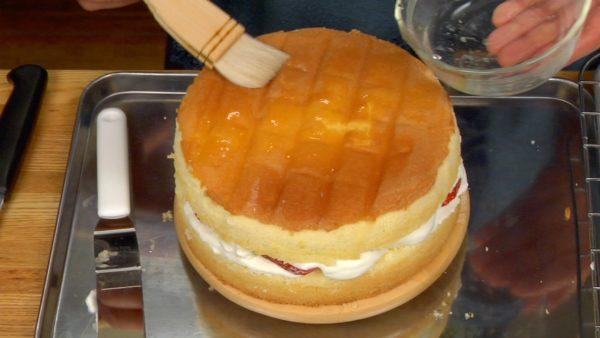 Legt nun den Tortendeckel mit der Sirupseite nach unten auf die Torte. Bestreicht die Oberfläche nun auch mit Sirup.