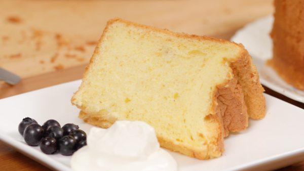 Cut a piece of cake. And place it onto a plate along with the blueberries and whipped cream. Finally, sprinkle on the icing sugar.