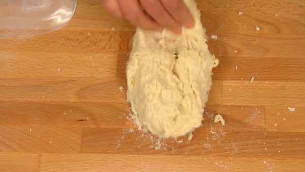 Throw the dough on the pastry board, fold it away, grab the side of the dough and throw it again. Gather the dough with the scraper. Knead the dough with your hands using your body weight. Repeat this process until the dough is less sticky.