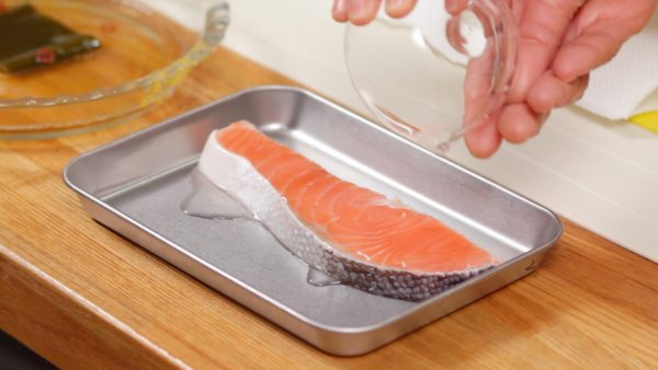 Let's make the Salmon Yakizuke. Add the sake to the salmon. And coat both sides evenly.