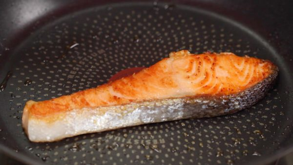 When the bottom is golden brown, flip it over. Brown the other side. You can also grill the salmon to give the skin a crisp texture, making the dish more delicious. Now, it is ready.