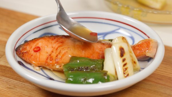 Garnish with the bell pepper and the long green onion. Finally, spoon the marinade over the salmon.