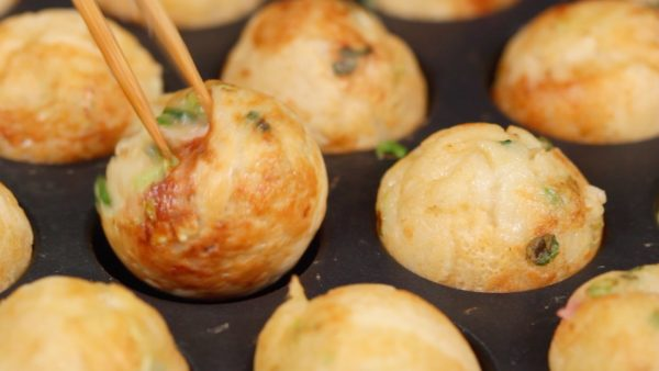 Now, the takoyaki are golden brown and turn smoothly with a light flick. Place each takoyaki onto a plate as soon as it is ready.