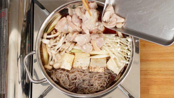 しらたき、1.5cmの厚さに切った焼き豆腐、長ねぎを入れます。えのきだけ、しめじも加えます。鶏肉を入れます。