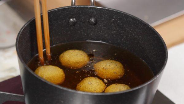 Friggiamo i dango. Scaldate in una pentola l'olio tra i 140 e i 150° C e immergeteci i dango. Con degli utensili ruotateli mentre si cuociono. Questo aiuterà a fare si che si gonfino uniformemente dandogli una forma tonda e un colore uniforme.