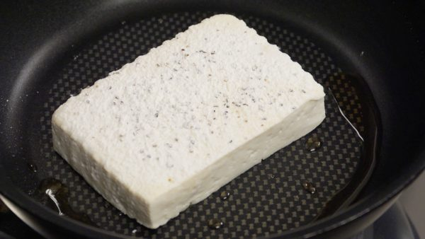 Add the sesame oil to a pan and turn on the burner. Place the tofu into the heated pan and saute the bottom.
