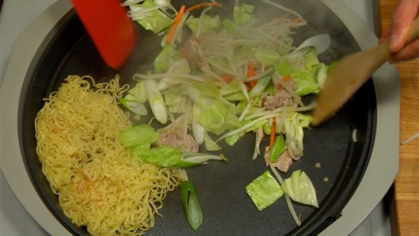 When the pork becomes brown, add the bean sprouts, cabbage leaf, long onion and carrot at one time. Lightly stir and sprinkle with salt and pepper. Mix with the spatula.