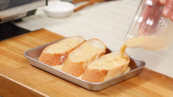 """Place 2.5cm (1"""") thick slices of baguette in a tray and pour the custard mixture over them. Make sure both sides are completely soaked with the custard mixture. Let the bread sit for 3 to 5 minutes."""