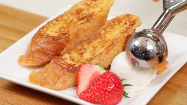 When both sides are golden brown, arrange the French toast onto a plate. The strawberry looks great as a garnish but orange or kiwi fruit can also be used.Spoon the ice cream next to the french toast.