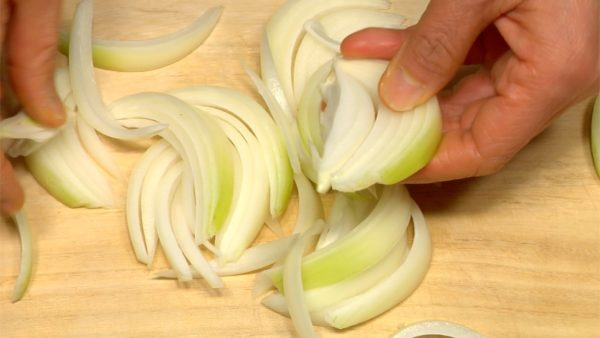 "Let's prepare the ingredients for Gyudon. Cut the onion into 1cm (0.4"")  wedges. Separate the layers with your fingers. Grate the ginger root. Cut the scallions into fine pieces."