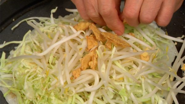 Layer the moyashi bean sprouts on the cabbage. Crumble on the ikaten, deep-fried dried squid coated with batter.