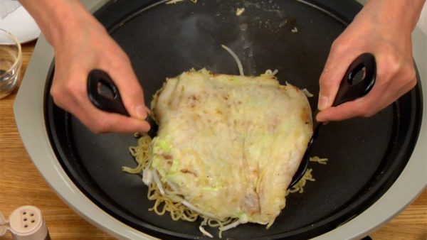 Lift the okonomiyaki with the turners and place it onto the noodles.