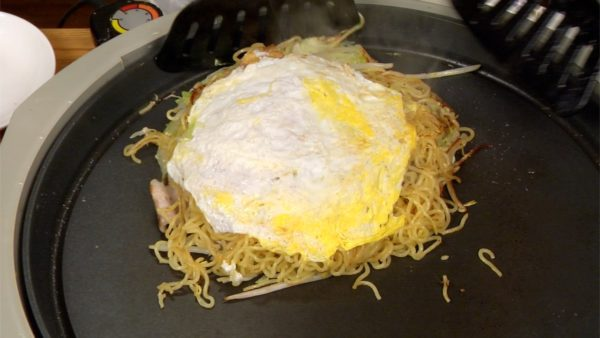 Quickly place the okonomiyaki onto the fried egg and then flip it over.
