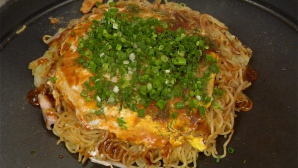 Coat the okonomiyaki with a generous amount of okonomiyaki sauce. Sprinkle on the bonito powder and the aonori seaweed. Finally, top with the chopped spring onion leaves and now it is ready to serve.