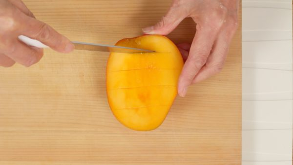 Slice off the mango along the flat seed and make cuts in the flesh in a grid pattern. Be sure not to cut the skin. By the way, this mango is from Miyazaki Prefecture. It is sweet and juicy but also expensive so we only used it for the topping.