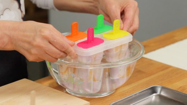 The popsicles are fully frozen. Dip the molds in a bowl of water for a moment or run them under water at the sink. This will help loosen the popsicles easily.