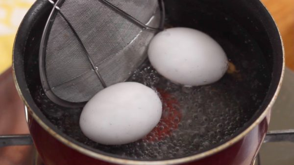 Let's make the half boiled eggs. Reduce the heat to low and carefully place 2 eggs into a pot of boiling water. During the first 2 minutes, gently rotate the eggs to help the yolks to stay in the center. Boil the eggs for a total of five and a half minutes.