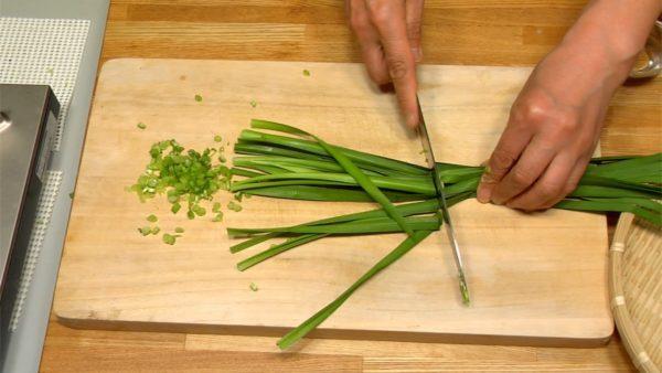 Hachez les tiges de la ciboulette chinoise d'abord. Coupez ensuite les feuilles en deux et hachez-les. Râpez la gousse d'ail et le gingembre.