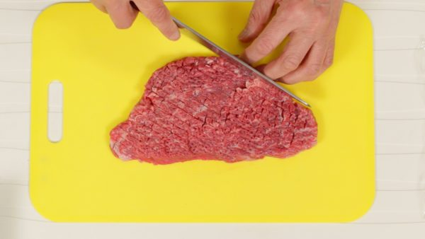 """Make numerous cuts along the steak, making a 5mm (0.2"""") grid pattern. Flip it over. And make a grid pattern again but be careful not to separate the steak."""