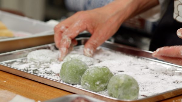 Tightly close the edges of the mochi. Repeat the process to wrap the rest of the anko balls.