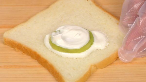 Let's make the fruit sandwiches. Spoon the yogurt cream onto the sliced bread. Place the sliced kiwi fruit onto the cream layer and then cover it with the cream.