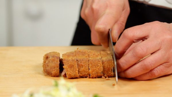 Let's cut the Gyukatsu into smaller, bite-size pieces. Make a cut in the breaded surface and then quickly slice off the meat. This will help to avoid breaking the outer layer.