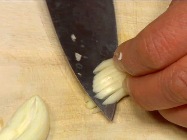 Découper la gousse d'ail en deux dans sa longueur. Retirer le germe. Faire des découpes verticales puis perpendiculairement aux premières découpes et hacher l'ail en petits morceaux.