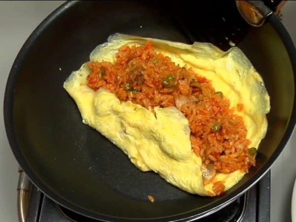Déposer le riz sauté au poulet sur l'omelette et plier les deux côtés afin d'emballer le riz. Découper l'omurice vers le bord.