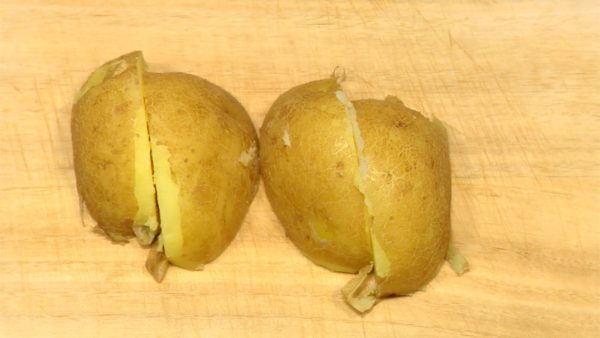 Cut the steamed potato into 4 pieces. Cut the tomato in half and slice it into half moons. Grate the garlic clove.
