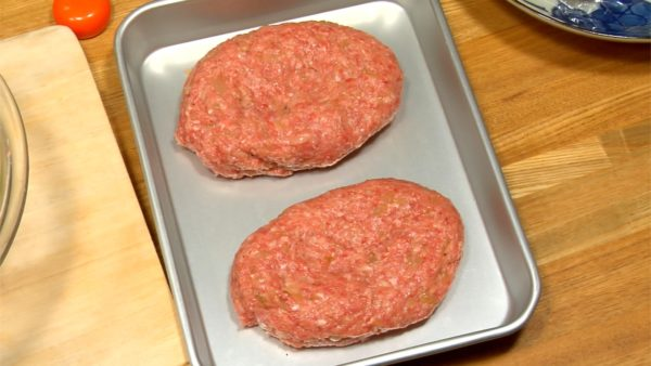 Shape it into an oval and flatten its center part. Place it on a baking tray. Repeat the process to shape another meat ball. If the meat mixture is too soft to shape, let it cool down in a fridge.
