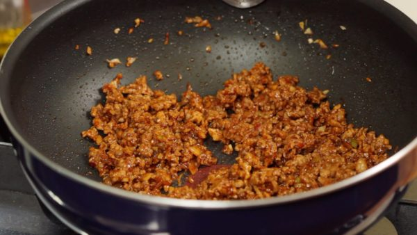 Distribute it evenly and stir-fry until the liquid is reduced almost completely. Place the meat mixture into a bowl.