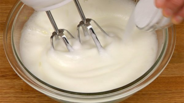 Let's make the batter for the roll cake. Using a hand mixer, beat 4 egg whites in a bowl. When the white is foamy as shown, add half of the sugar. Beat it again and then add the rest of the sugar.