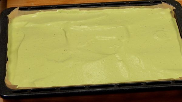 With a scraper, distribute the batter to the edges. Be careful not to break the foam and gently spread it evenly. Drop the baking sheet a few times to break any air bubbles in the batter.