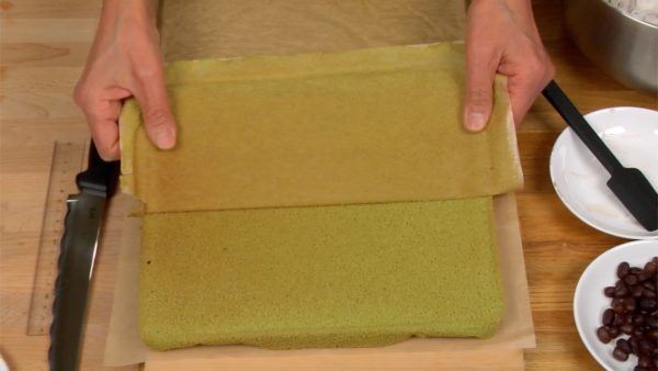 Release the edges of the paper from the cake. Cover the top of the cake with another sheet of paper and then flip it over. Carefully, peel off the paper from the bottom of the cake.