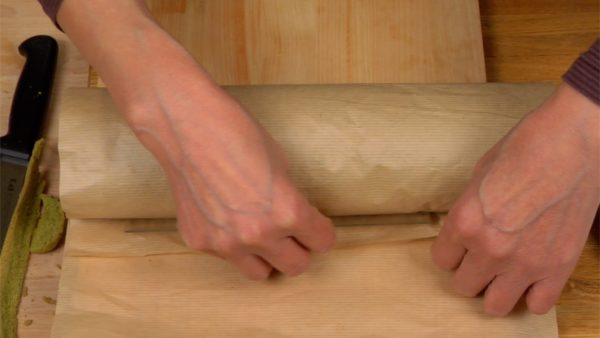 Remove the paper and wrap the roll cake with another sheet of paper. Using a ruler, tightly wrap the roll cake as shown in the video. Make sure to place the cake with the seam-side down.