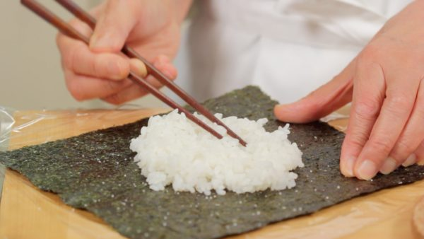 Let's make the onigirazu. Place a sheet of toasted nori seaweed onto plastic wrap and sprinkle on salt. Then, place half the rice onto the nori and distribute. Use hot steamed rice so that you can easily shape it.