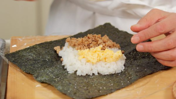 Arrange the tori soboro onto one side of the rice. Then, arrange the iri tamago onto the other side.