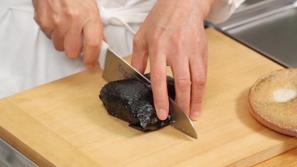 Now, the nori and rice have firmly attached together. Remove the plastic wrap. Dampen the knife to help to make a clean cut and cut the onigirazu in half crosswise.