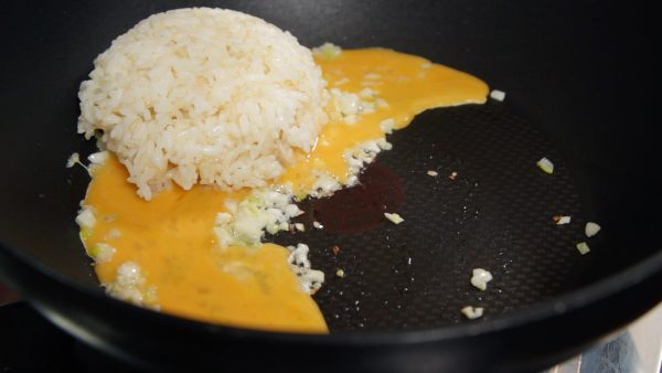 Add the beaten egg and the hot steamed rice.