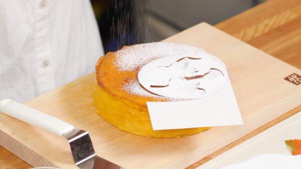 ではチーズケーキの飾り付けをします。敷紙を取り除いて型紙をケーキにのせます。粉砂糖を振りかけます。